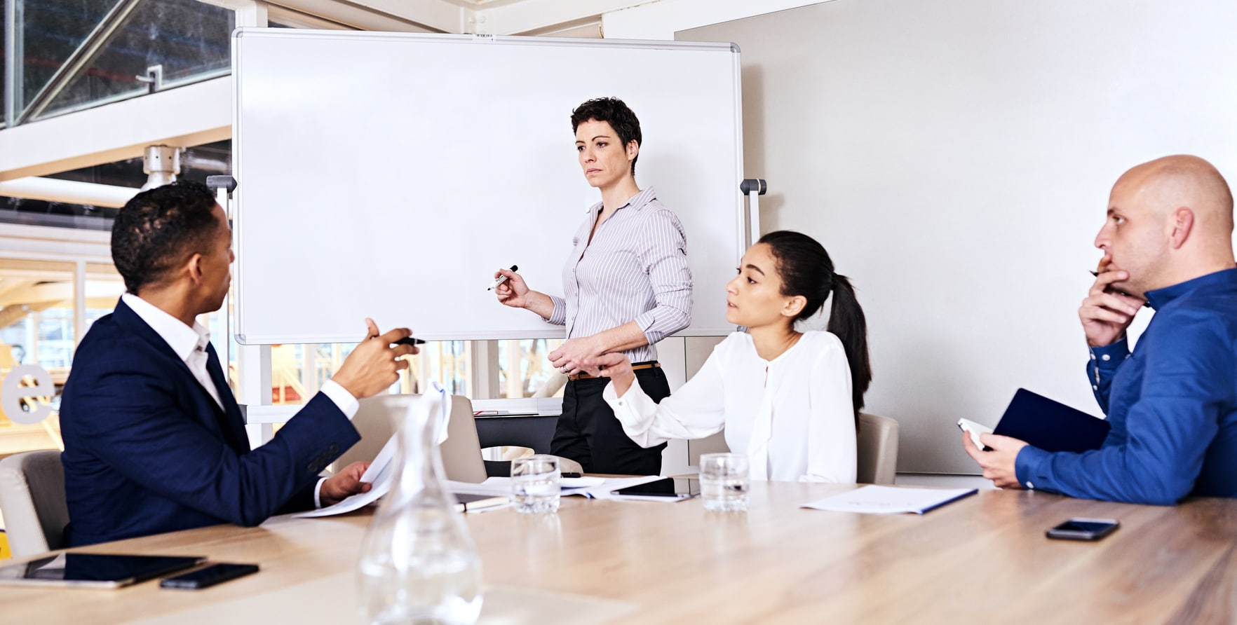 Mature business woman paying attention to a fellow colleague as he answers a question that the businesswoman asked with the other two board members paying close attention to their partners.