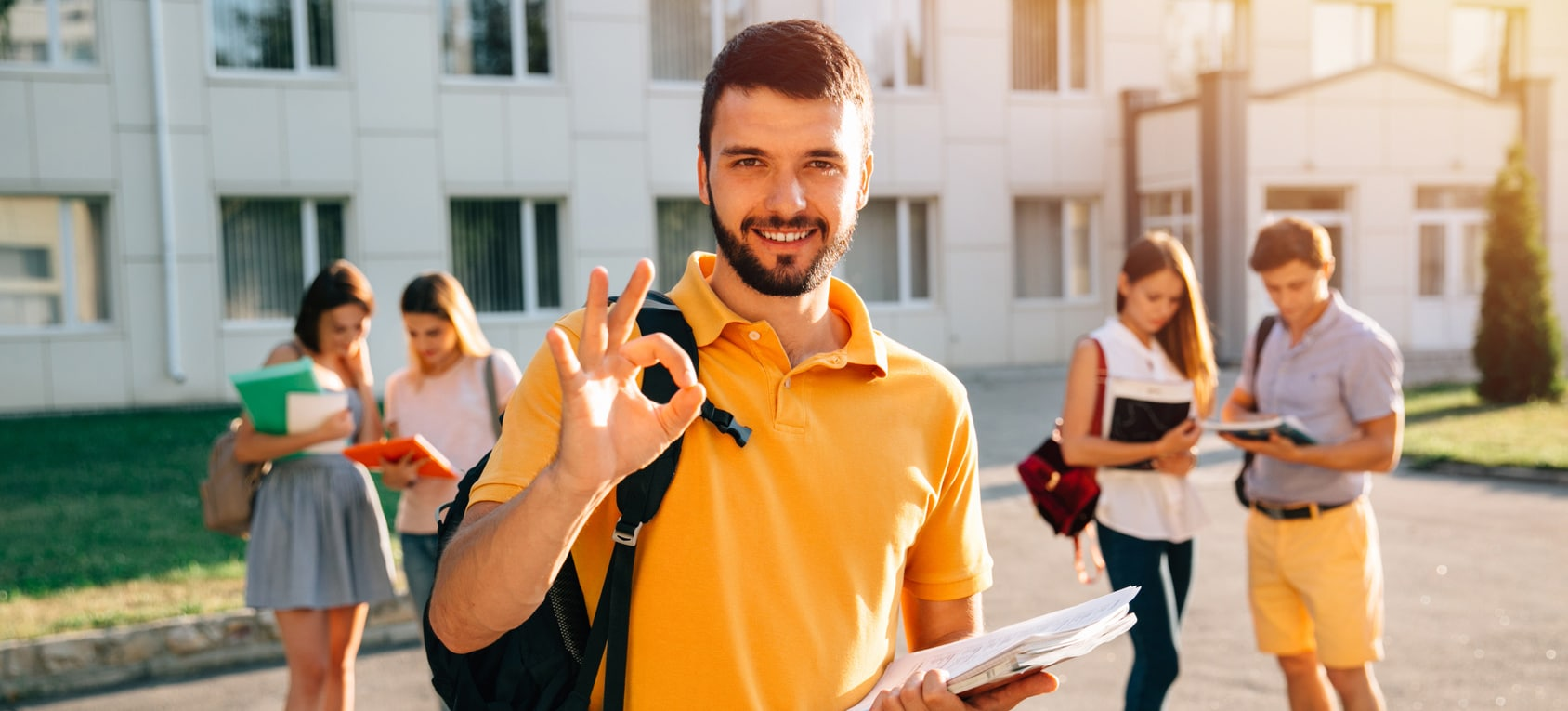 Happy student with note-books and backpack smiling and showing okay while standing on background of university and friends